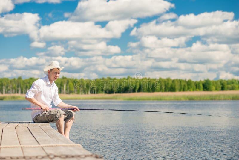 Portrait d'un pêcheur dans un chapeau sur un pilier en bois sur un beau photographie stock