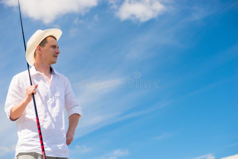 Portrait d'un pêcheur rural avec une canne à pêche dans un chapeau sur un b image stock
