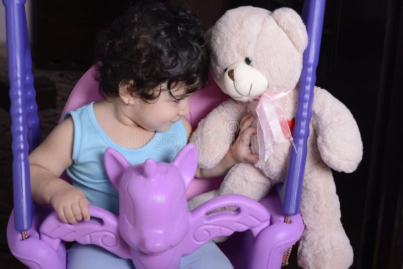 Portrait d'un petit bébé sur l'oscillation de licorne avec le C.A. de jalousie photographie stock