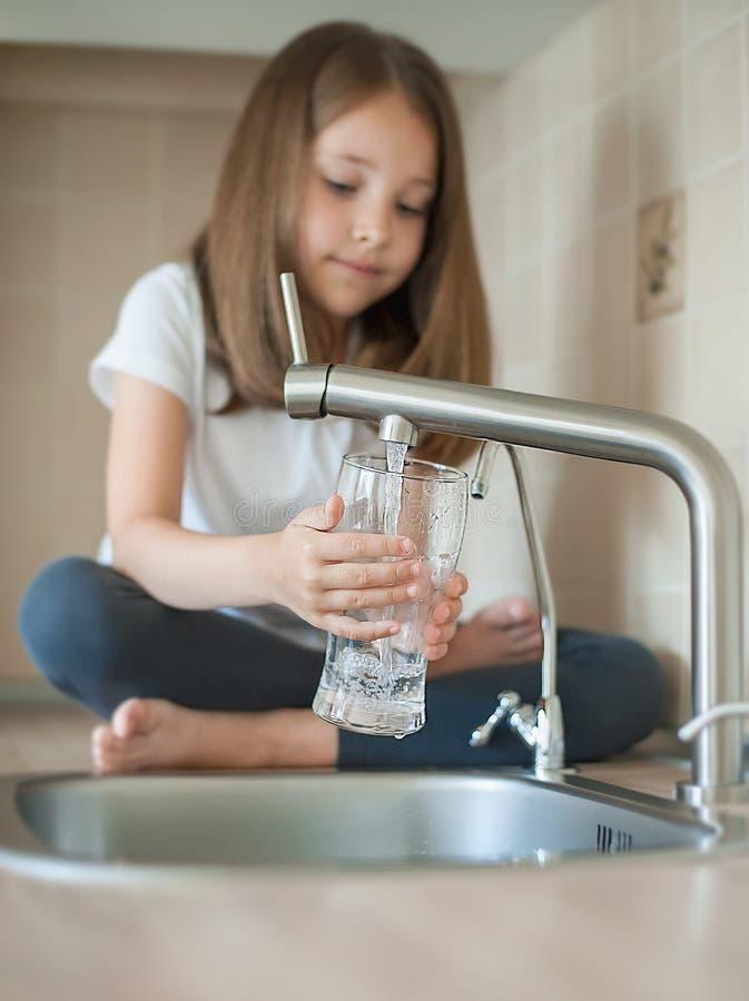 Portrait d'un petit b?b? caucasien tenant un verre d'eau propre du robinet Robinet de cuisine Eau douce de versement d'enfant mig image stock