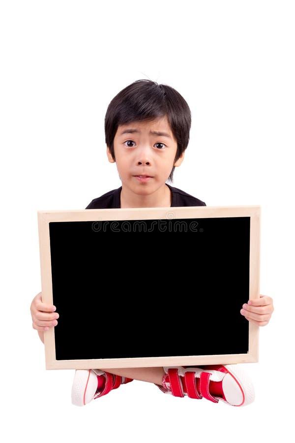 Portrait d'un petit garçon étonné tenant un panneau d'affichage photographie stock