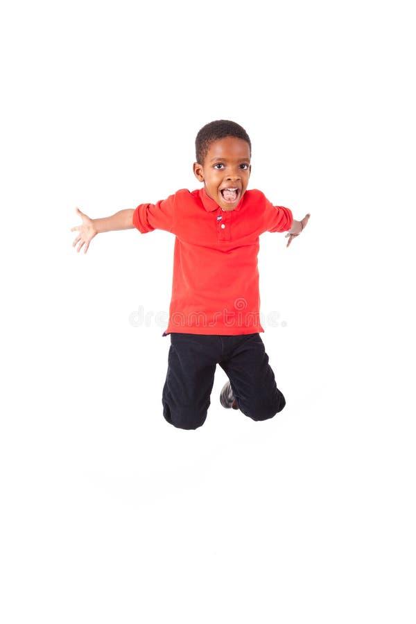 Portrait d'un petit garçon d'afro-américain mignon sautant, d'isolement image stock