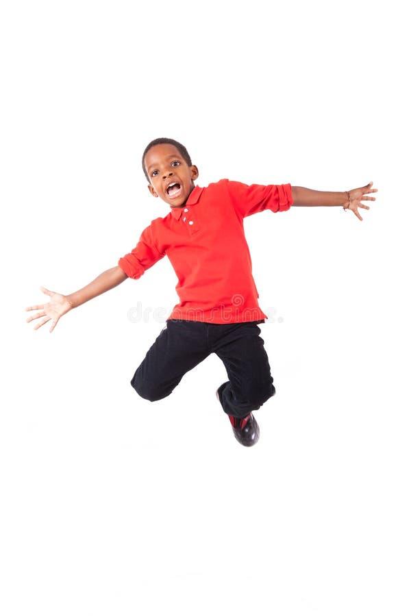 Portrait d'un petit garçon d'afro-américain mignon sautant, d'isolement photographie stock