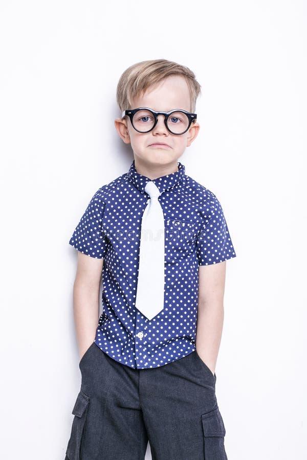 Portrait d'un petit garçon dans des verres et un lien drôles école précours Mode Portrait de studio d'isolement au-dessus du fond images libres de droits