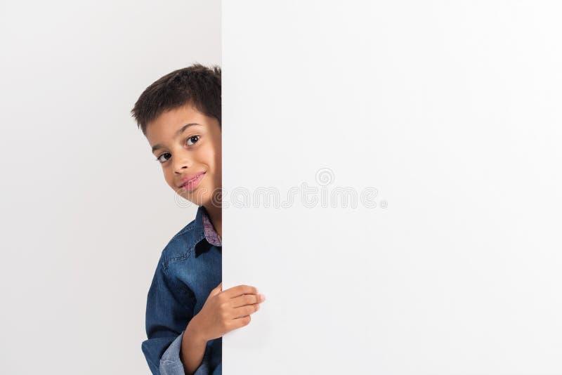 Portrait d'un petit garçon heureux tenant un conseil vide sur le fond blanc photographie stock libre de droits