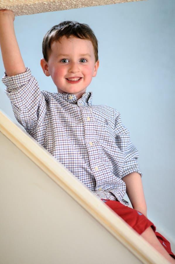 Portrait d'un petit garçon mignon à l'intérieur sur des escaliers photo stock