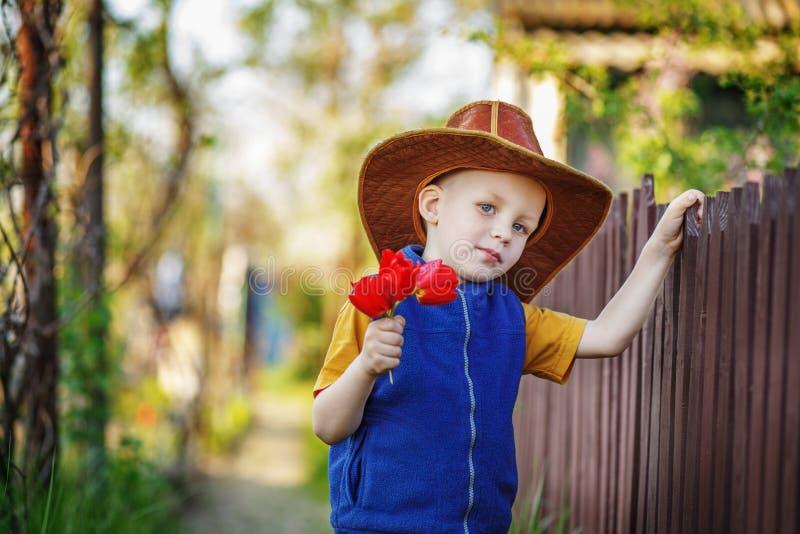 Portrait d'un petit garçon se tenant dans un grand chapeau avec un bouquet de images stock