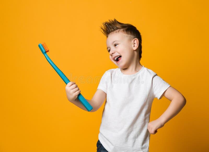 Portrait d'un petit garçon tenant une brosse à dents au-dessus de fond jaune photo libre de droits