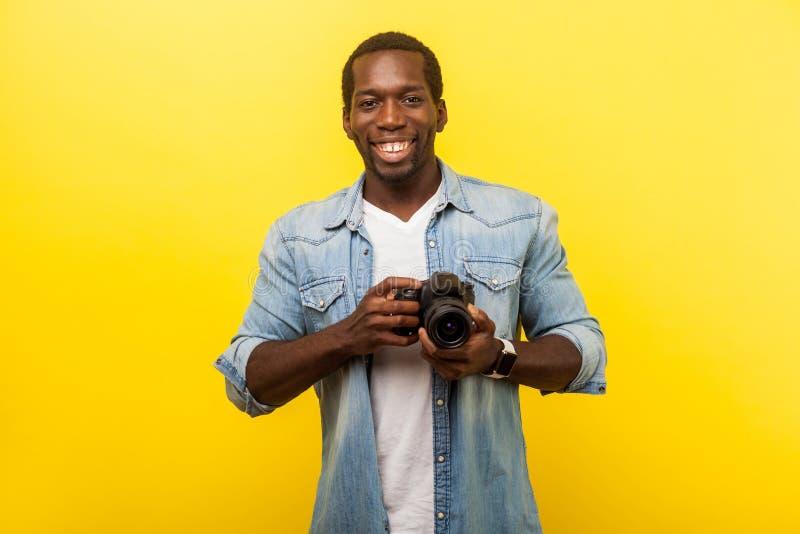 Portrait d'un photographe positif, homme joyeux en chemise denim tenant un appareil photo numérique professionnel isolé sur jaune photographie stock