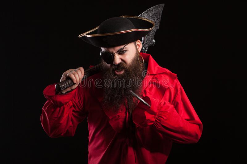 Portrait d'un pirate barbu médiéval sur le fond noir images stock