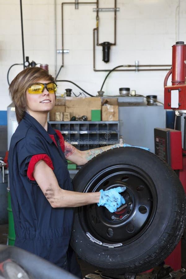 Portrait d'un pneu de transport de jeune mécanicien féminin sûr dans l'atelier de réparations de véhicule photographie stock libre de droits