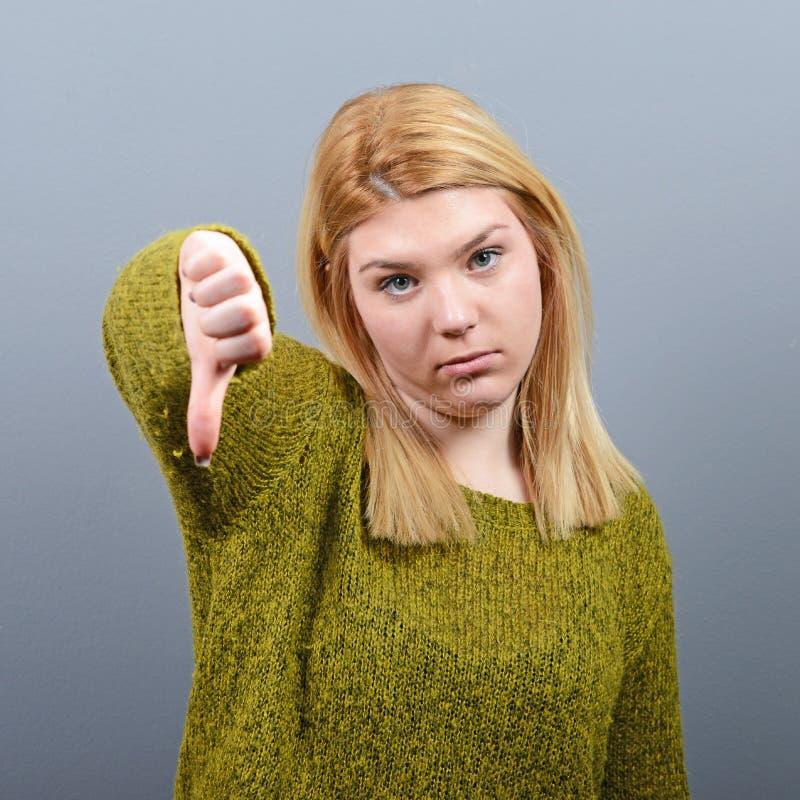 Portrait d'un pouce d'apparence de femme vers le bas comme désapprobation sur le fond gris photo stock