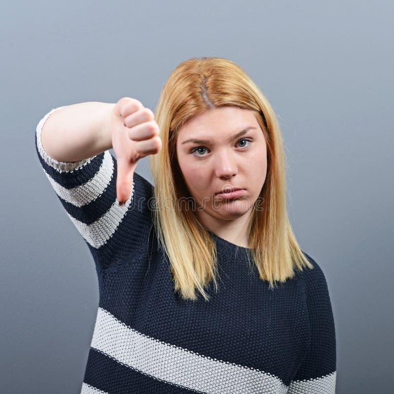 Portrait d'un pouce d'apparence de femme vers le bas comme désapprobation sur le fond gris image libre de droits