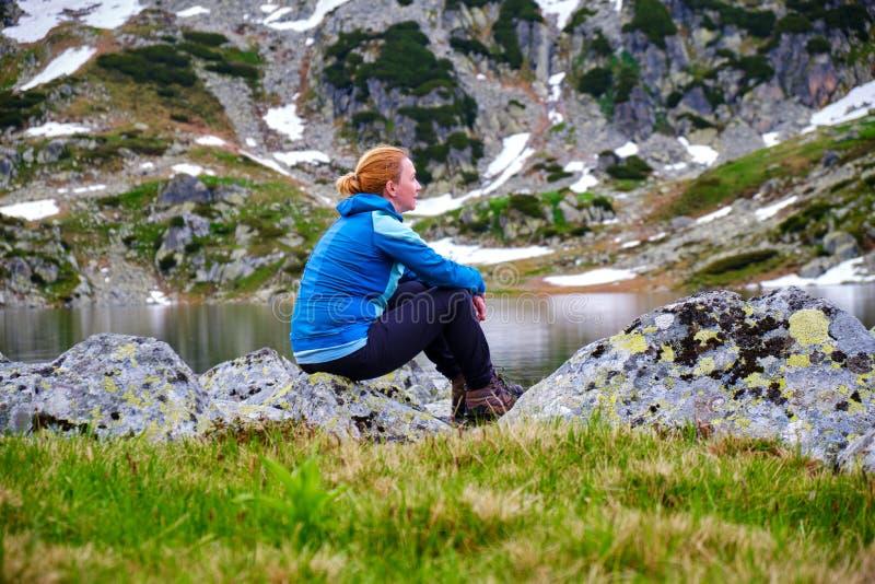 Portrait d'un randonneur mélancolique de femme au lac Bucura de montagne, dans la pièce de montagnes de Retezat de Carpathiens, l photographie stock libre de droits