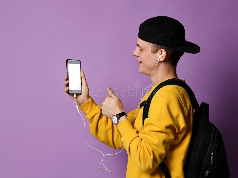 Portrait d'un sac ? dos de port d'?tudiant gai, dans le chapeau et les verres et le smartphone d'utilisation au-dessus du fond po photos stock