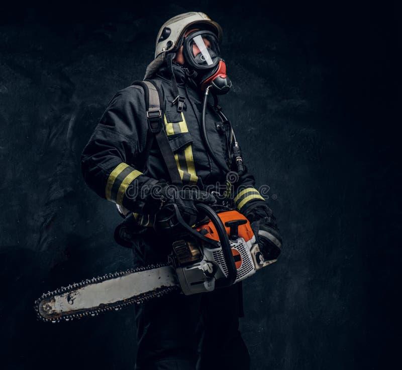 Portrait d'un sapeur-pompier dans le casque de sécurité et du masque à oxygène tenant une tronçonneuse Photo de studio contre un  images stock