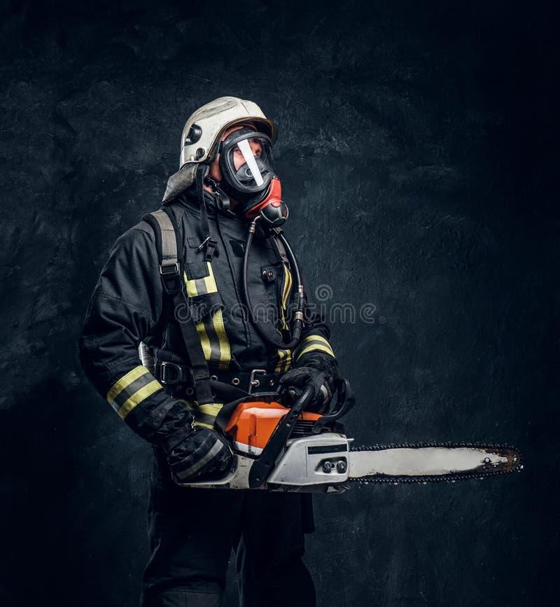 Portrait d'un sapeur-pompier dans le casque de sécurité et du masque à oxygène tenant une tronçonneuse Photo de studio contre un  photographie stock libre de droits