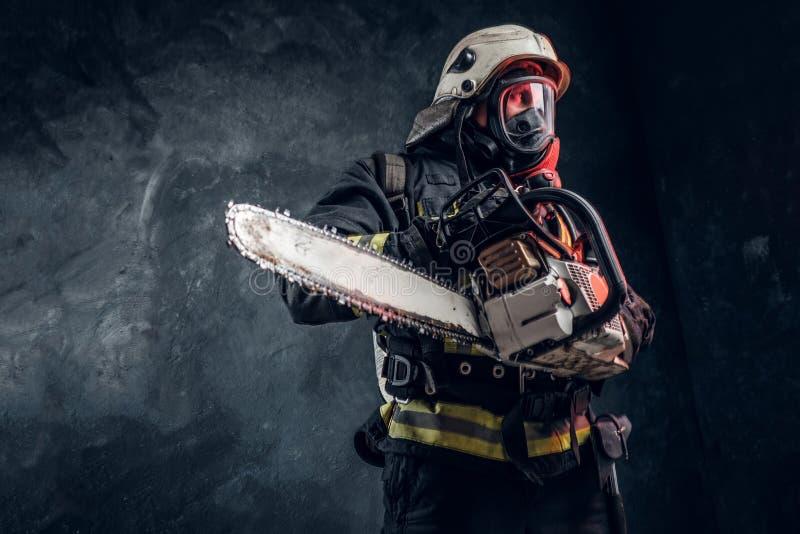 Portrait d'un sapeur-pompier dans le casque de sécurité et du masque à oxygène tenant une tronçonneuse Photo de studio contre un  photo libre de droits