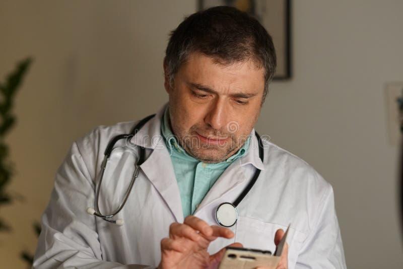 Portrait d'un service de mini-messages de docteur à son téléphone portable photographie stock libre de droits