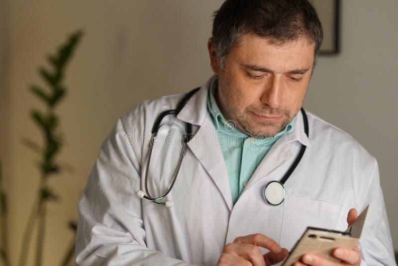 Portrait d'un service de mini-messages de docteur à son téléphone portable image stock
