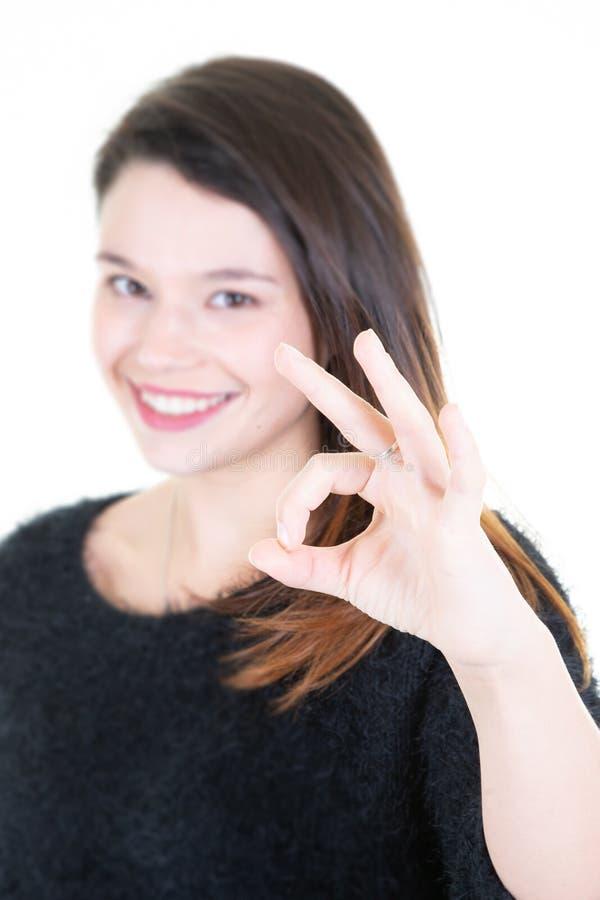 Portrait d'un signe correct de sourire et de regarder de femme de victoire heureuse d'apparence la caméra sur le fond blanc photo stock