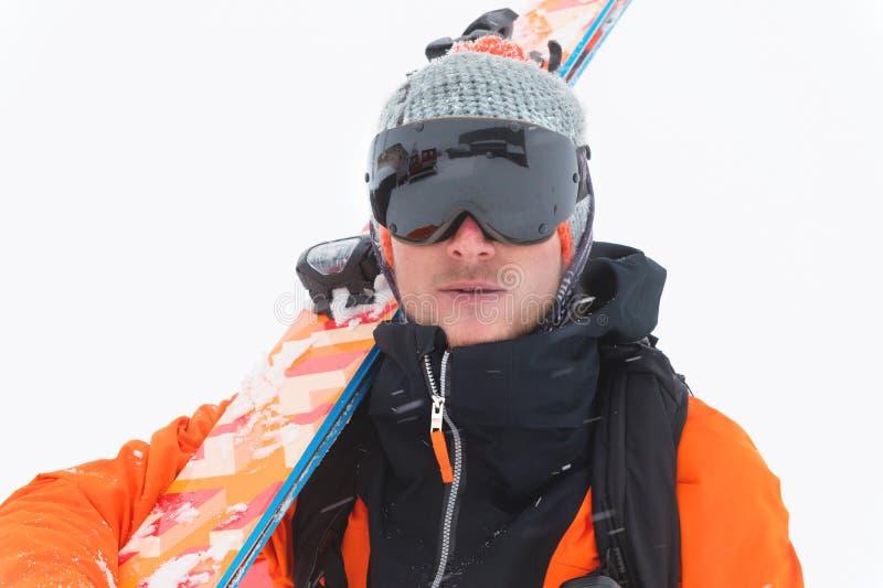 Portrait d'un skieur professionnel d'athlète dans une veste orange portant un masque noir et avec des skis sur ses regards d'épau image libre de droits