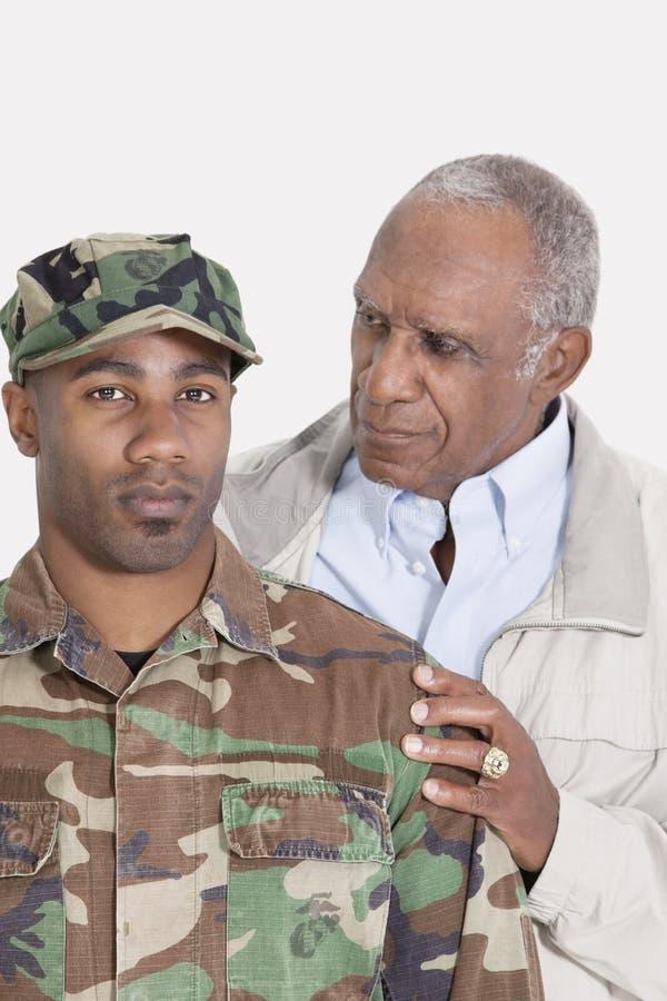Portrait d'un soldat des USA Marine Corps d'Afro-américain avec le père au-dessus du fond gris images stock