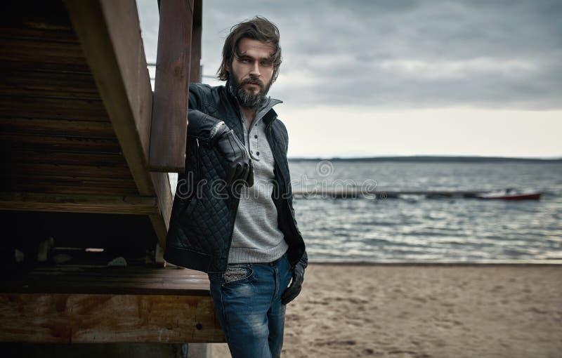 Portrait d'un type beau mûr se reposant sur la plage d'automne photos libres de droits
