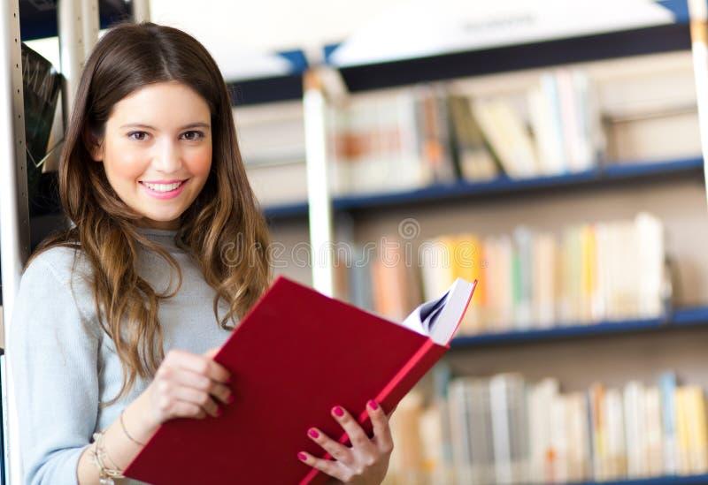 Étudiante dans une bibliothèque photo stock