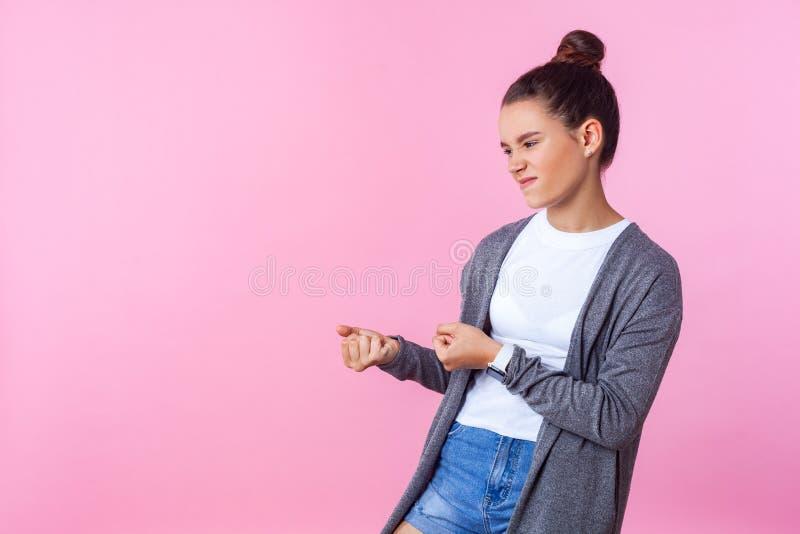 Portrait d'une adolescente brunette persistante faisant semblant de tirer avec un gros effort fond rose, espace de copie photo libre de droits