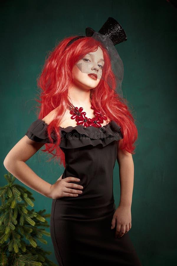 Portrait d'une adolescente dans une robe noire avec une perruque rouge et dans un chapeau de carnaval An neuf de Noël image libre de droits