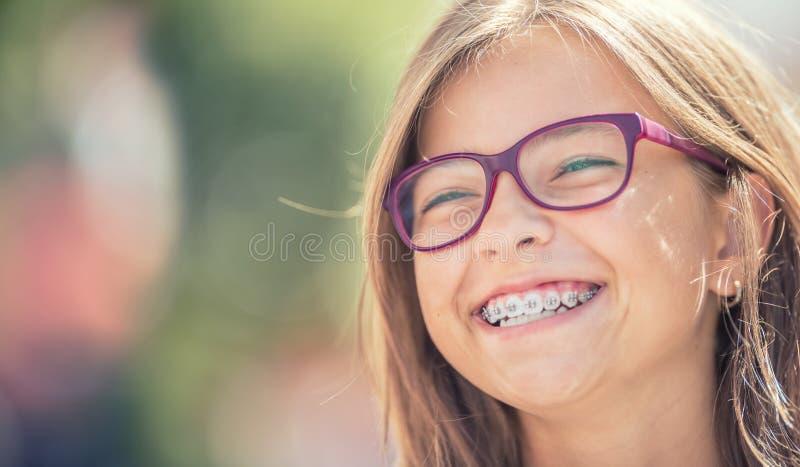 Portrait d'une adolescente de sourire heureuse avec des bagues dentaires et photographie stock