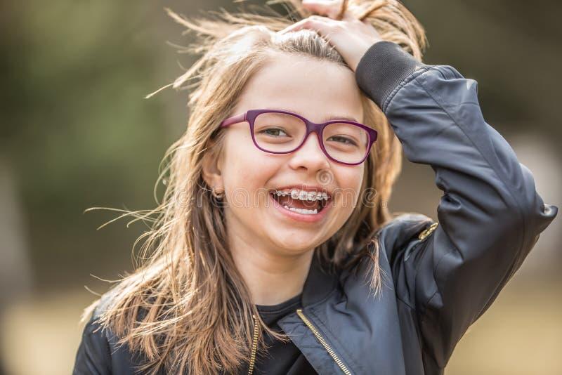 Portrait d'une adolescente de sourire heureuse avec des bagues dentaires et des verres photo libre de droits