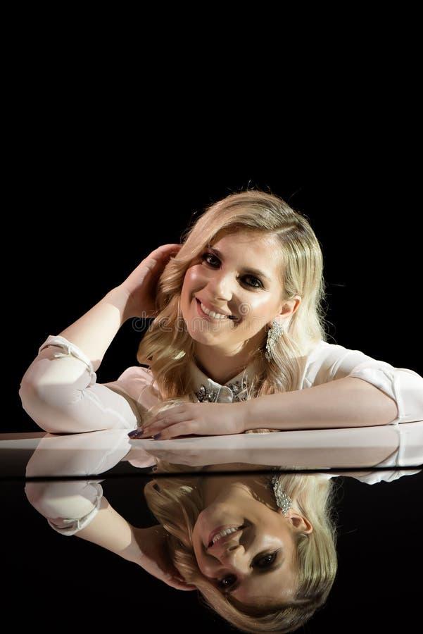 Portrait d'une belle actrice pr?s d'un piano blanc photographie stock