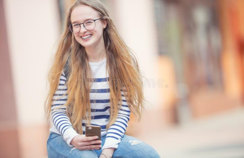 Portrait d'une belle adolescente de sourire avec des bagues dentaires Jeune écolière avec le sac et le téléphone portable d' photos stock