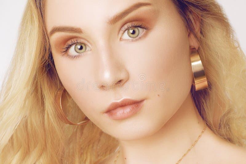 Portrait d'une belle blonde avec de longs cheveux Fille avec des boucles d'oreille d'or, bijoux observe le vert de fille Projecti photo stock