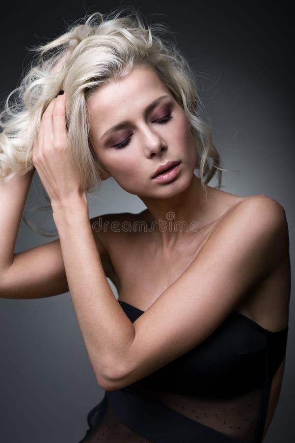 Portrait d'une belle blonde redressant ses cheveux avec ses mains photos libres de droits