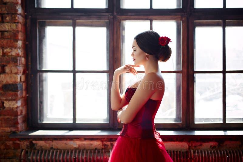 Portrait d'une belle danseuse de jeune femme dans une robe rouge près de la fenêtre photos libres de droits