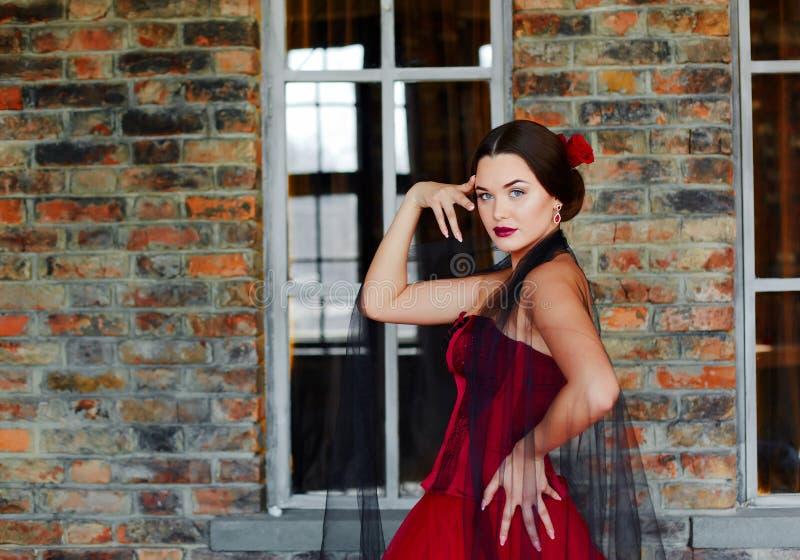 Portrait d'une belle danseuse de jeune femme dans une robe rouge près de la fenêtre photo libre de droits
