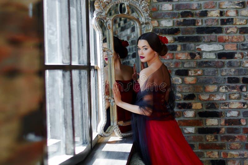 Portrait d'une belle danseuse de jeune femme dans une robe rouge près de la fenêtre image stock