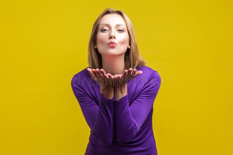 Portrait d'une belle et belle jeune femme envoyant un baiser d'air isolé sur fond jaune photographie stock libre de droits