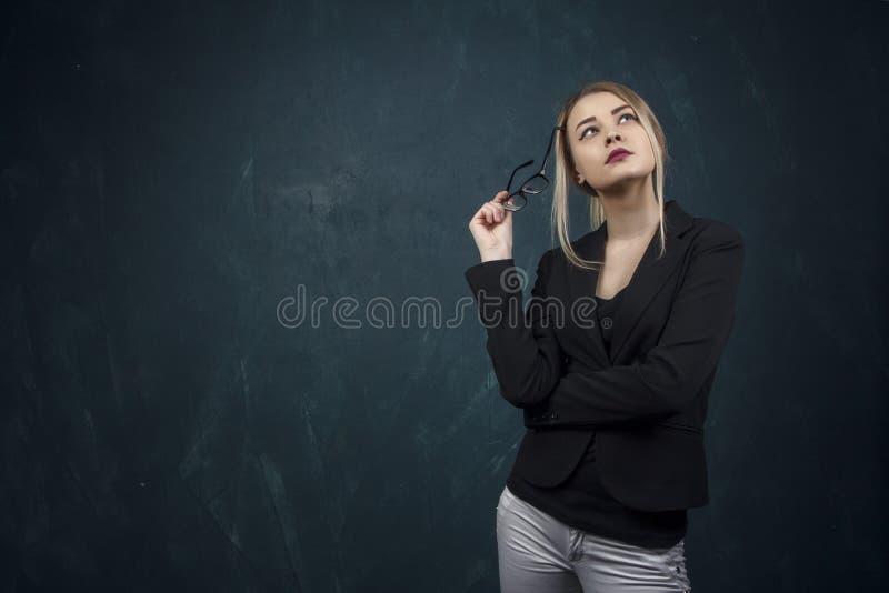 Portrait d'une belle femme avec des lunettes de soleil dans des mains et de costume contre un mur de texture bleu avec l'endroit  photos stock
