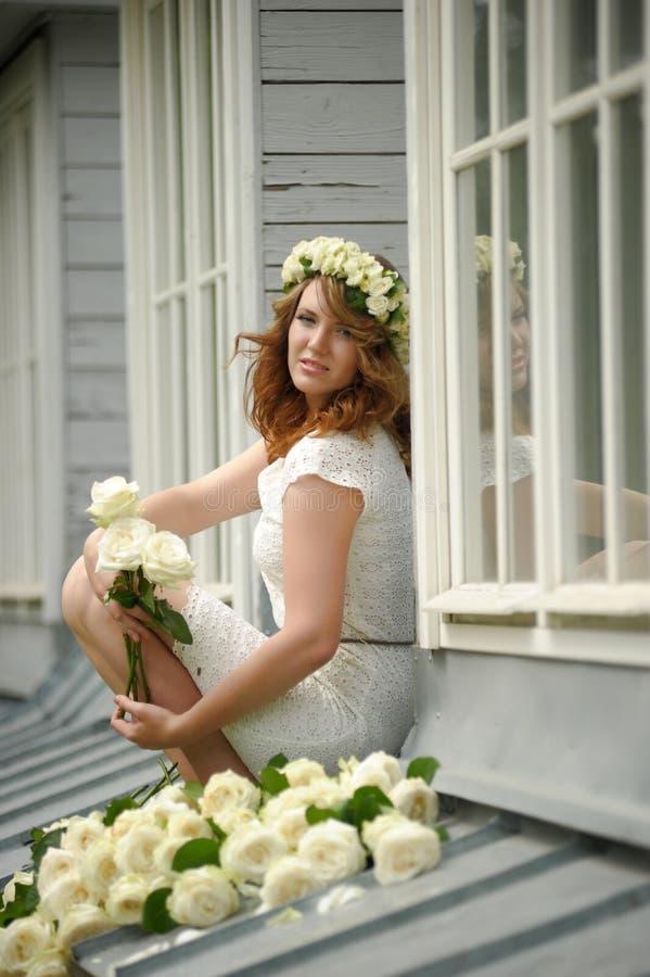 Portrait d'une belle femme avec un bouquet des roses blanches image libre de droits