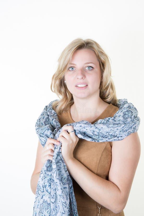 portrait d'une belle femme blonde dans la robe brune et l'écharpe bleue photographie stock libre de droits