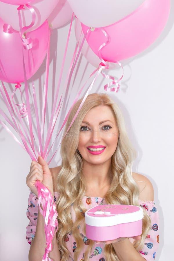 Portrait d'une belle femme blonde tenant un cadeau, avec les boules roses et blanches Satisfait un cadeau, surprise célébration image stock