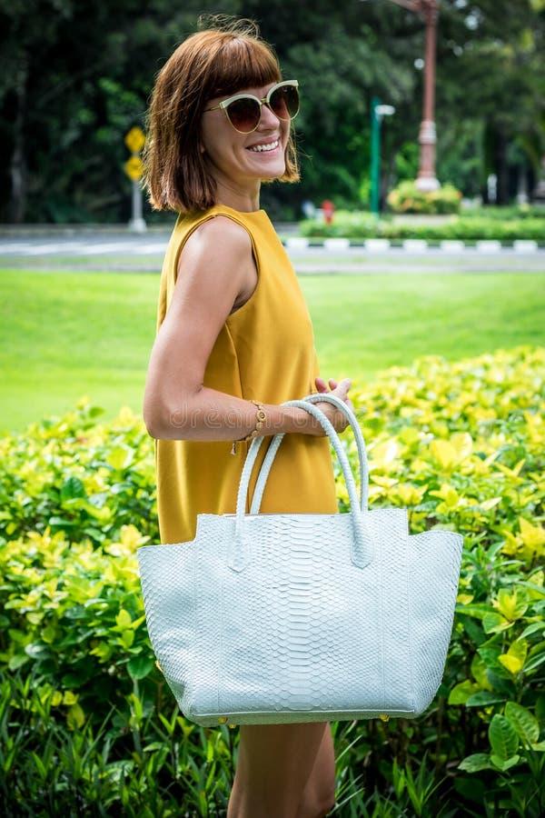 Portrait d'une belle femme caucasienne à la mode de brune avec des lunettes de soleil et la pose de luxe de sac à main de python  photos stock