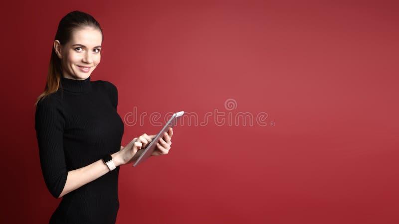 Portrait d'une belle femme caucasienne de sourire dans une robe noire utilisant un comprim? sur un fond rouge photographie stock
