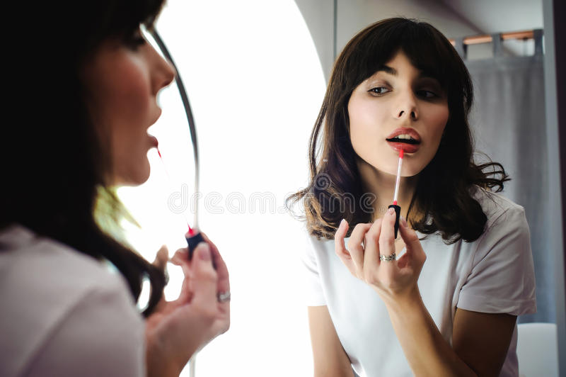 Portrait d'une belle femme, colorants son rose de rouge à lèvres de lèvres, regardant dans le miroir images stock