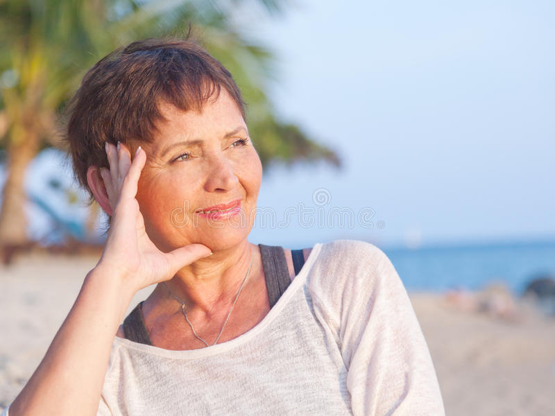Portrait d'une belle femme d'une cinquantaine d'années sur la plage images stock