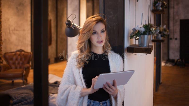 Portrait d'une belle femme dans l'intérieur, les utilisations un smartphone ou le comprimé d'accéder à l'Internet image libre de droits